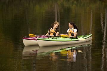 Two young women kayaking on Oxtongue Lake in autumn, Mukoka, Ontario, Canada.