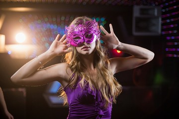 Woman with masquerade dancing on dance floor