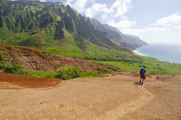 A lone male hiker descending to Kalalau beach on the Kalalau Trail, Kaua'i