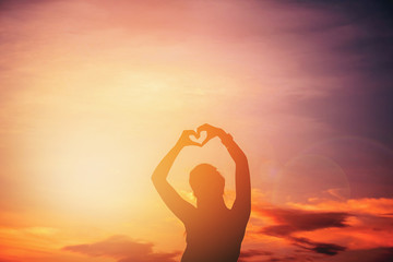 Women hands forming a heart with sunset silhouette