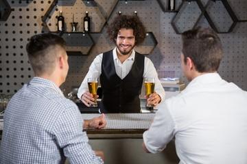 Bartender serving beer to customers