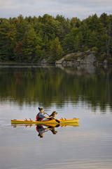 Young man kayaking with dog on Gull Lake near Gravenhurst, Ontario, Canada.