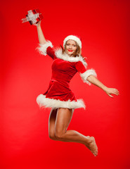 christmas, x-mas, winter, concept - smiling woman in santa helper hat with gift box, happiness jump for joy over red background