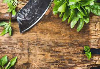 Tuinposter Kruiderij Fresh green basil and vintage herb chopper on rustic wooden bord, top view, copy space, horizontal composition