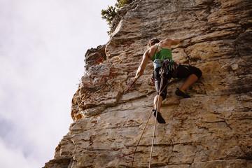 Woman climbing rock, Castle Mountain, Canada