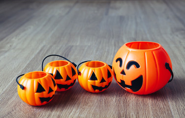Group of happy and smiling jack-o-Lantern pumpkin buckets on wood background