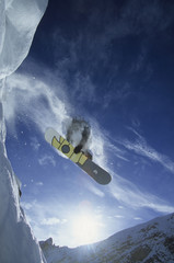 Low angle view of a snowboarder catching some air in the backcountry, Golden, British Columbia, Canada