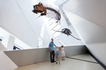 Dad with little girl and boy looking at dinosaur fossils at Royal Ontario Museum, Toronto, Ontario, Canada