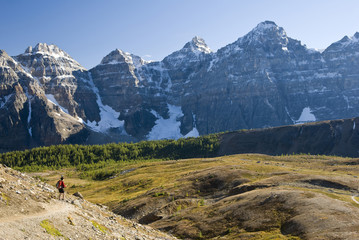 A female hiker looks out over Larch Valley on the trail to Sentinel Pass near Moraine Lake, Banff National Park, Alberta, Canada.