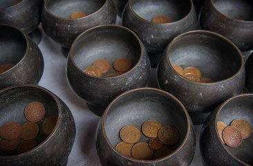 Monk's alms bowl and Thai coin donated for happiness and good luck, Thailand.
