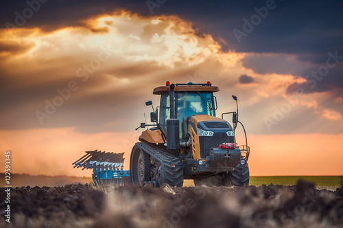 Wall mural Farmer in tractor preparing land with cultivator