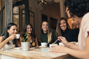 Smiling women having coffee and chatting