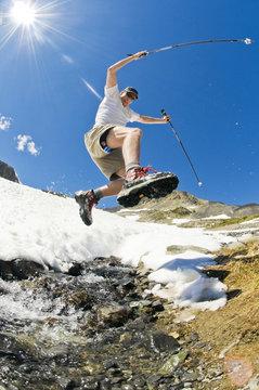 A hiker leaps across an alpine stream above Garibaldi Lake in Garibaldi Provincial Park, BC.