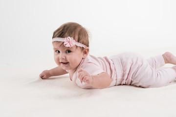 Glückliches Baby liegt spielend auf Boden