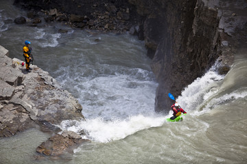 A male kayaker drops a large waterfall on the Bighorn River, Nordegg, Alberta, Canada