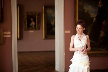 Thoughtful bride in transparent dress adjusts her bracelet while