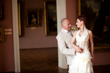 Bride with short red hair looks over her shoulder at groom while
