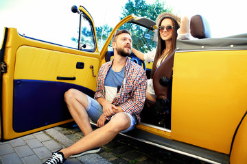 Beautiful young couple talking and smiling while standing near their new convertible