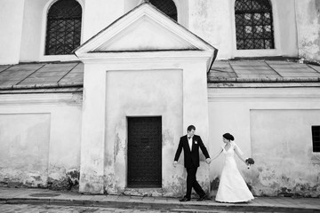 Black and white photo of eye-catching wedding couple walking alo