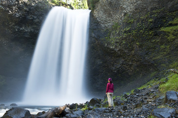 A woman stands beside Moul Falls in Wells Gray Provincial Park, BC. Model release signed.