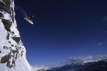 A snowboarder jumping off a cliff, Marmot Basin, Alberta, Canada.