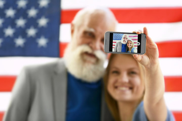 Grandfather and granddaughter taking picture on American flag background