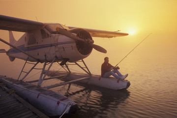 man fishing from float plane, along Red River, Manitoba, Canada
