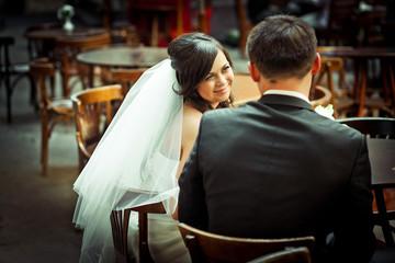 Charming brunette bride looks over her shoulder at groom sitting
