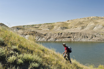hiker, South Saskatchewan River Valley with Lake Diefenbaker in the background, near Beechy,  Saskatchewan, Canada