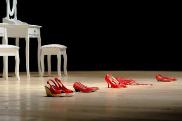 Scarpe rosse su un palco, simbolo della violenza sulle donne