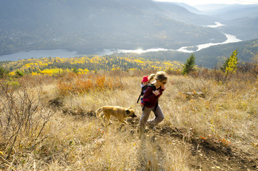 A young woman, carrying her child and hiking with a dog above the Kootenay River up Nelson's Pulpit Rock Trail, Nelson, British Columbia