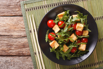 Asian salad with fried tofu, tomatoes and arugula close-up. horizontal top view