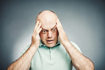 middle-aged man put his hand to his head complains, with shocked