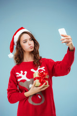 Girl dressed in santa hat with a Christmas gift and phone