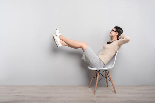Joyful woman resting in the chair