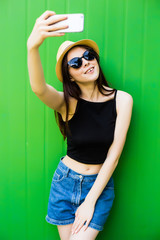 Smiling summer woman take selfie with hat and sunglasses over bright background.