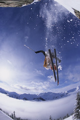 A skier catching some air after jumping a cliff in the backcountry of Kickinghorse Resort Area, Golden, British Columbia, Canada