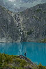 A young woman hikes in front of a blue lake and waterfall in the Niut Range, British Columbia, Canada