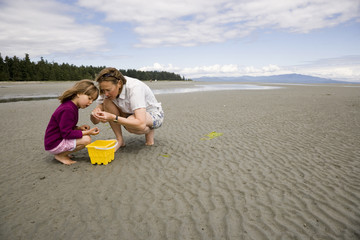 Young mother with 5-year old daughter, collect shells on beach at low tide, Parksville, British Columbia, Canada.