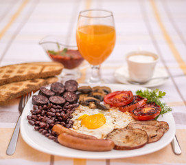 Full English fried breakfast with bacon, egg, sausages, black pudding, mushrooms, grilled tomatoes and baked beans. Closeup with toasts, cappuccino, orange juice and home made  red sauce.