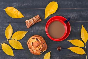 Сup of coffee and a cinnamon bun with amongst autumn leaves