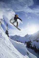 A snowboarder catching air of rock cliff in the backcountry in Golden, British Columbia, Canada.