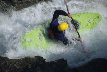 A river kayaker squeezing through the narrow gap on Beauty Creek, Alberta, Canada.
