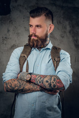 Portrait of bearded traveller male with tattooed arms.