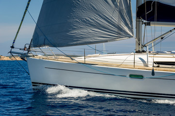 Sailboat bow with hoisted genoa is sailing in the Mediterranean