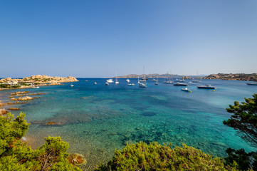 Scenic bay with turquoise water and sailing boat anchorage.