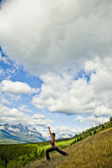 A young woman practicing yoga on a hill above the town of Canmore, AB