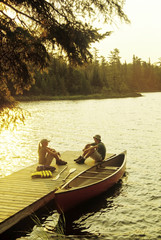 Teens on dock, Lyons Lake, Whiteshell Provincial Park, Manitoba, Canada.