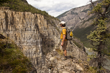 Man on cliff face above Nahanni River near 'The Pulpit' rock formation, Nahanni National Park Preserve, NWT, Canada.