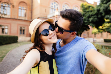 Happy smiling couple kissing and taking selfie